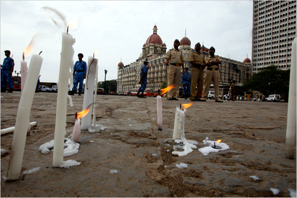 Indian policemen walked past flowers and candles in front of the Taj Mahal Hotel.
