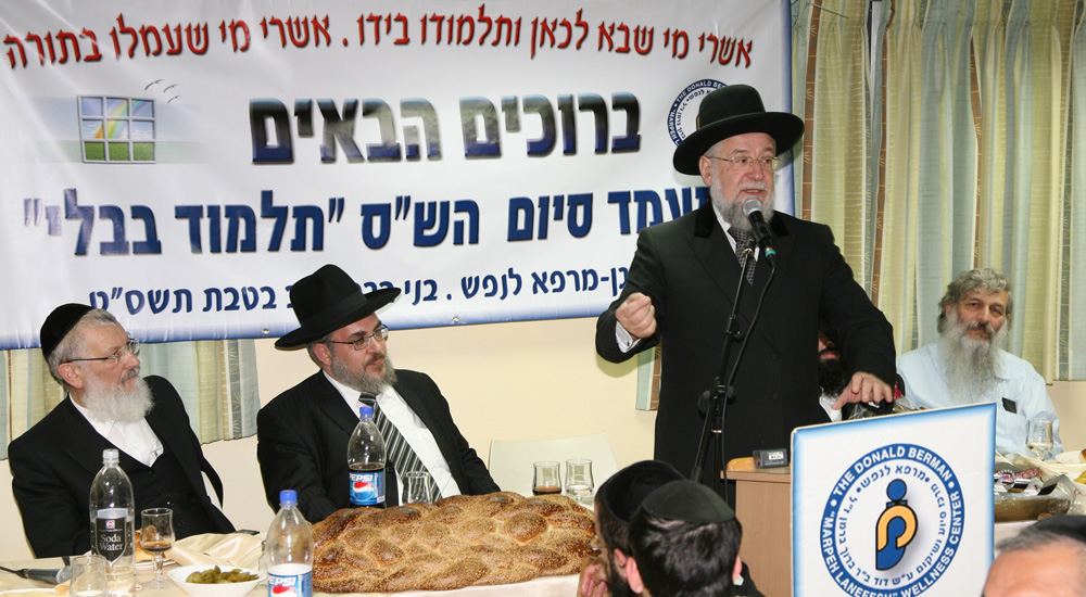 Rabbi Lau at the microphone, sitting L is Rav Yaakov Asher, mayor of Bnei Brak the yeshiva student sitting on the right behind Rabbi Lau has been phased out of the photo to protect his identity.
