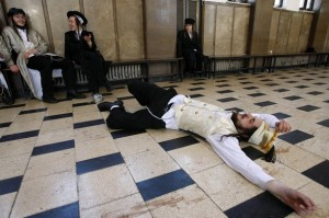 Reuters FILE - An ultra-Orthodox Jew lies on the ground drunk during celebrations for the Jewish holiday of Purim in a synagogue in Jerusalem March 23, 2008.