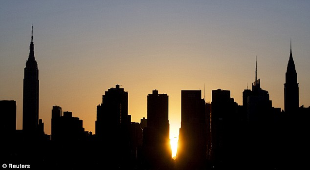 Modern-day marvel: The sun sets over Manhattan aligned exactly with the streets in a phenomenon known as Manhattanhenge