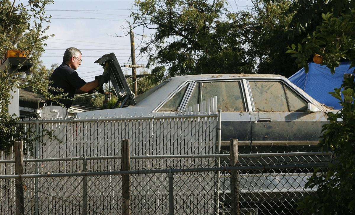 An FBI agent inspects the car that was reportedly used in the kidnapping of Jaycee Dugard as it is being impounded from the home of 58-year-old Phillip Garrido and his 54-year-old wife Nancy Garrido in Antioch, Calif.