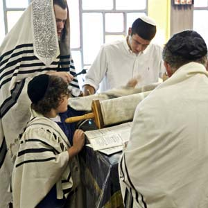 Blake Glover, 13, participates in his bar mitzvah. Unlike more mainstream Jewish groups, where boys learn to recite lengthy passages from the Torah to complete the initiation, Ultra-Orthodox bar mitzvahs put emphasis on the passage as a beginning of learning. Photo by Christine Lockerby