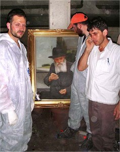 Jewish volunteers stand around a portrait of the Lubavitcher Rebbe, Rabbi Menachem Mendel Schneerson, amidst the ruined Beit Chabad in Mumbai. The Picture of the Rebbe unscathed in attack