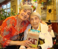 Holocaust survivor Jafa Wallach is pictured with her daughter Rena Bernstein on her 100th birthday, Dec. 28, 2009. She is holding her memoir, Bitter Freedom. Eagle photo by Phoebe Neidl