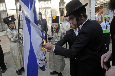 Member of an anti-Zionist group called Neturei Karta burn an Israeli flag on the Jewish holiday of Purim in Mea Shearim, Jerusalem, March 11, 2009.