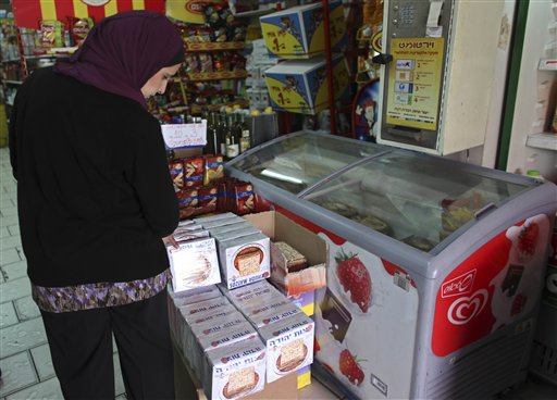 A Palestinian woman looks at boxes of matzoh in a grocery store in Abu Gosh, near Jerusalem, Thursday, April 1, 2010. Israel's Arab minority has developed a love affair with matzoh, the dry, crunchy wafers that observant Jews eat as a substitute for leavened bread during the weeklong holiday of Passover. Weeks before the holiday, Arab-owned stores across Israel stock up on matzoh, knowing their customers will clean it out. (AP Photo/Tara Todras-Whitehill)