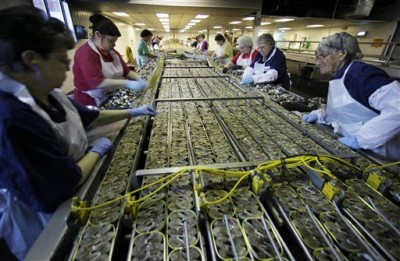 In this Thursday, April 8, 2010 photo, workers fill cans with sardine steaks at the Stinson sardine cannery in Gouldsboro, Maine. The cannery, the last of its kind in the U.S., will shut down this week. (AP Photo/Robert F. Bukaty)