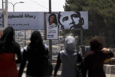FILE - Palestinian girls walk near a billboard with a picture of U.S. President Barack Obama, in the West Bank city of Ramallah, Monday, May 3, 2010.