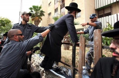 Israeli riot police remove an ultra-Orthodox Jew from a fence as they make arrests on 16 May 2010 at Barzilai Medical Center in the southern town of Ashkelon, Israel. EPA/