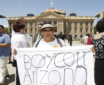 FILE - This April 29, 2010 file photo shows Josephine Nevarez, of Phoenix, holding a sign in protest.  Arizona is facing a backlash over its new law cracking down on illegal immigrants. (AP Photo/Ross D. Franklin, File)
