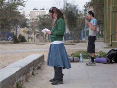 In this March 10, 2010 photo an Israeli hiker prays as another eats after spending the night at a school in Dimona and before a day of hiking along the Israel Trail in the Negev desert, southern Israel. Many countries have hiking trails. But few are so small that you can walk clear across them in two months or less, and even fewer have landscapes so varied that they allow a hiker to pass from desert hills of red stone to flat wastelands to green forests and lakes and rugged mountain tops in such a short period of time.     (AP Photo/Maya Hasson)