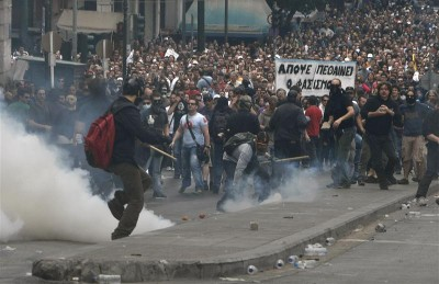 Athenian demonstrators hurl projectiles at riot police in Athens during a nationwide strike in Greece, May 5, 2010.  Greece braced for a day of demonstrations during a nationwide strike by civil servants protesting the announcement of draconian austeristy measures.   REUTERS/John Kolesidis