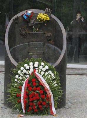 """A wreath in Poland's national colors, white and red, marks a new monument honoring Jewish insurgents of the Warsaw Ghetto Uprising that was unveiled in Warsaw, Poland, on Thursday May 13, 2010. The bronze memorial depicts a sewage canal with disembodied hands symbolically climbing their way to freedom. Combatants escaped from the ghetto to the city's """"Aryan"""" side in 1943 through sewage canals. (AP Photo/Czarek Sokolowski)"""