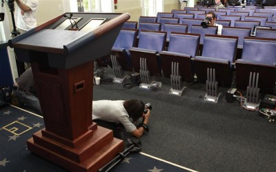 FILE - Photographers get pictures of the seat of veteran White House reporter Helen Thomas in the White House briefing room in Washington June 7, 2010. Thomas, who has covered every administration since Eisenhower's and occupies front-row center in the White House briefing room, has resigned after recently making controversial comments on Israel. REUTERS/Kevin Lamarque