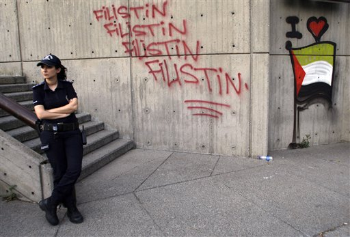 "A police officer stands in front of graffiti reading ""Palestine"", during a demonstration outside the Israeli consulate in Istanbul, Tuesday, June 1, 2010. Israel's deadly raid on a Gaza-bound aid ship has ignited unprecedented anger in Turkey and driven the Jewish state's relations with its most important Muslim ally to their lowest point in six decades. (AP Photo/Ibrahim Usta)"