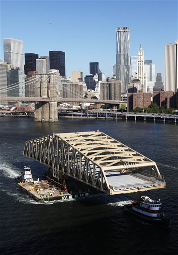 A 350-foot-long replacement bridge is floated on a barge on the East River as it passes the Brooklyn Bridge and the lower Manhattan skyline, Monday, July, 26, 2010, in New York. The bridge will replace the Willis Avenue bridge which connects Manhattan and the Bronx. (AP Photo/Mark Lennihan)