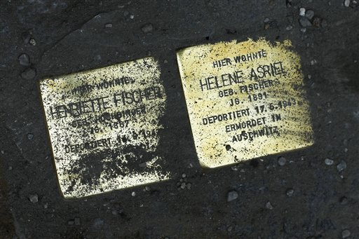 "Picture taken July 1, 2010 shows the so called 'Stolpersteine', or stumbling stones by German artist Gunter Demnig of Holocaust victims Henriette Fischer and Helene Asriel set into Genthiener Strasse street in Berlin, Germany.   Demnig has set more than 25,000 of these stumbling stones which are shiny brass plaques in the size of a child's hand and which mark the lives of people lost to the Nazis between 1933 and 1945,  fixed in front of places were they once lived before they were killed in the Holocaust. One of the stones reads ""Davisco Asriel lived here. Born in 1882. Deported 25.1.1942. Murdered in Riga."" Artist Demnig said ""It's a social sculpture and if you look at it as a whole, it is the biggest art monument in the world.""  (AP Photo/Markus Schreiber)"