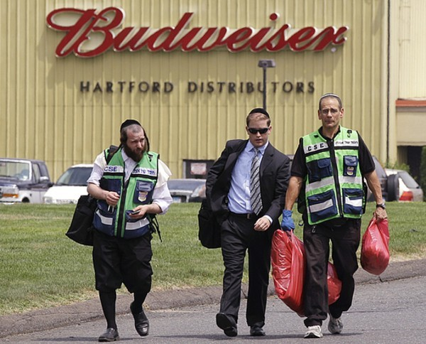 Chesed Shel Emes from NY Rabbi Mayer Berger, left, walks with a man carrying bags of blood-covered fabric outside the Hartford Distributors building, where a gunman killed eight and himself, in Manchester. According to Rabbi Berger, he was there to retrieve all the body remains of Louis Felder Jr., who was expected to be buried later in the day. Credit: AP