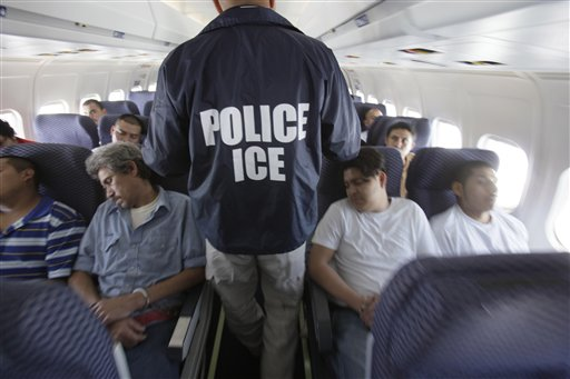 An Immigration and Customs Enforcement agent walks down the aisle among  shackled Mexican immigrants a boarded a U.S. Immigration and Customs Enforcement charter jet for deportation in the air between Chicago, Il. and Harlingen, Texas, Tuesday, May 25, 2010.  (AP Photo/LM Otero)