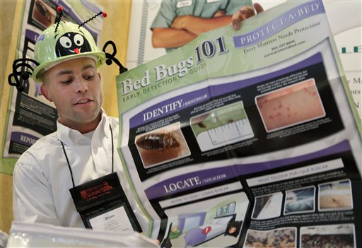 Brian Hirch, Sales Manager for Protect A Bed, wears a bed bug hard hat as he displays literature during the first North American Bed Bug Summit, Tuesday, Sept. 21, 2010, in Rosemont, Ill. The event's sponsor, BedBug Central, says the two-day summit will host 14 of the nation's leading entomologist and bed bug specialists, along with a gathering of bed bug-industry related vendors. (AP Photo/M. Spencer Green)