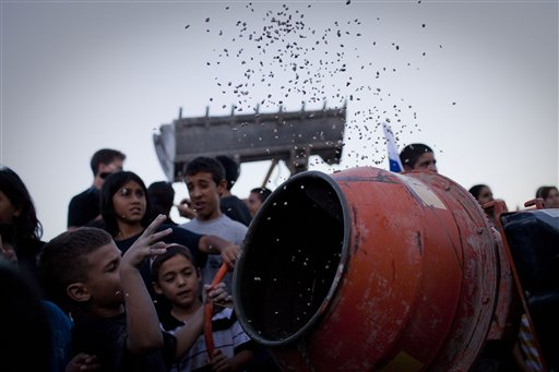 Jewish children throw material into a cement mixer during a symbolic ceremony to renew construction in the West Bank, in the Jewish settlement of Adam, near Ramallah, Wednesday, Sept. 1, 2010. Following Tuesday's fatal shooting, Jewish settler leaders said they would unilaterally resume construction in West Bank settlements on Wednesday evening. At Adam settlement near Jerusalem dozens gathered and prepared cement for the rebuilding. (AP Photo/Bernat Armangue)