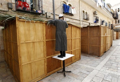 An ultra-Orthodox Jewish man covers the roof of a Sukkah with palm branches in Jerusalem's Mea Shearim neighbourhood September 21, 2010. A sukkah is a ritual booth used during the Jewish holiday of Sukkot, which begins Wednesday at sundown. REUTERS/Ronen Zvulun