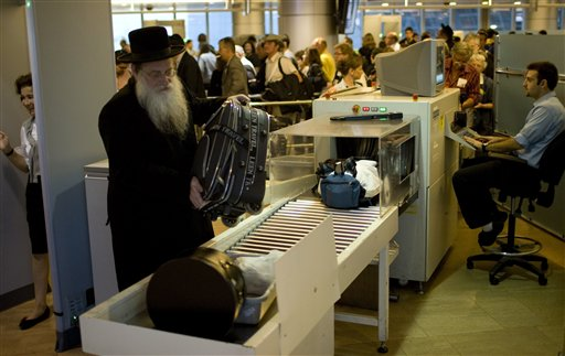 Passengers have their hand luggage screened by security personnel, inside the Ben Gurion air port terminal near Tel Aviv, Israel, Tuesday, Nov. 2, 2010. Senior Israeli airport official Nahum Liss said Tuesday screening procedures at airports around the world are inadequate, calling Israel's heavily fortified international airport the best protected in the world. (AP Photo/Ariel Schalit)