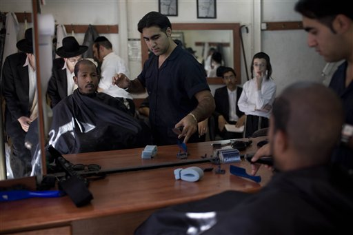 "U.S. rapper Jamal ""Shyne"" Barrow, second left, is seen reflected in a mirror as he gets his hair cut in a barber shop in the Orthodox Jewish neighborhood of Mea Sharim in Jerusalem, Friday, Nov. 12, 2010. The rapper Shyne is singing a new tune: After serving eight years in prison for a nightclub shooting, the former protege of Sean ""Diddy"" Combs has converted to Orthodox Judaism, come to Jerusalem, and is devoting his days to the study of Torah while plotting a musical comeback. (AP Photo/Tara Todras-Whitehi"