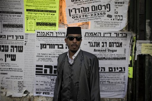 "U.S. rapper Jamal ""Shyne"" Barrow poses for a picture in front of posters of announcements in Hebrew in the Orthodox Jewish neighborhood of Mea Sharim in Jerusalem, Friday, Nov. 12, 2010. The rapper Shyne is singing a new tune: After serving eight years in prison for a nightclub shooting, the former protege of Sean ""Diddy"" Combs has converted to Orthodox Judaism, come to Jerusalem, and is devoting his days to the study of Torah while plotting a musical comeback. The Hebrew on the posters are death notices on the bottom and an ad for a kosher advertising company above. (AP Photo/Tara Todras-Whitehill)"