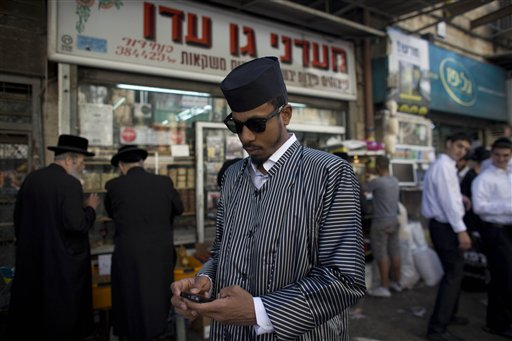 "U.S. rapper Jamal ""Shyne"" Barrow, center, checks his phone as he walks down the street in the Orthodox Jewish neighborhood of Mea Sharim in Jerusalem, Friday, Nov. 12, 2010. The rapper Shyne is singing a new tune: After serving eight years in prison for a nightclub shooting, the former protege of Sean ""Diddy"" Combs has converted to Orthodox Judaism, come to Jerusalem, and is devoting his days to the study of Torah while plotting a musical comeback. (AP Photo/Tara Todras-Whitehill)"