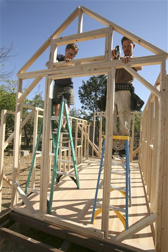 In this photo taken Oct. 14, 2010, Jay Schafer, owner of Tumbleweed Tiny Houses, left, works on construction of a frame with worker Zeke Gifford in Graton, Calif. In a country where most people want to live large,  Schafer helps people live small. The California homebuilder has become a leader in a small but growing corner of the American housing market: the tiny house. Schaefer, who lived in a 89-square foot house with his wife before his son was born last year, builds houses that are smaller than most people's living rooms.  (AP Photo/Ben Margot)