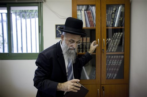Israeli Rabbi Mordechai Nagari who recently signed a religious ruling barring Jews from selling or renting homes to non-Jews, takes a book from his cabinet in his office as he poses for a photo, in the Jewish West Bank settlement of Maaleh Adumim near Jerusalem, Tuesday, Dec. 7, 2010. Three dozen of Israel's top rabbis have thrown their support behind a religious ruling barring Jews from selling or renting homes to non-Jews - testifying to a growing radicalism within the rabbinical community at a time when frictions between Israeli Arabs and Jews are mounting. (AP Photo/Tara Todras-Whitehill)