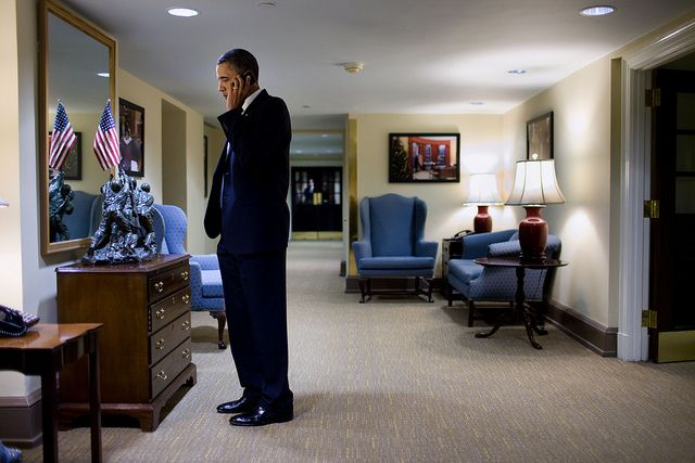 President Barack Obama on a cell phone in the hallway outside the Situation Room of the White House