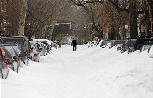 FILE - In this Dec. 28, 2010 file photo, a man walks down the center of a snow-filled street in the Brooklyn borough of New York. The city has cleaned up from big storms before with ease, but this blizzard became unlike anything New Yorkers had seen in decades. (AP Photo/Seth Wenig, File)