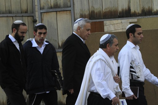 Former Israeli President Moshe Katsav, center, leaves is house to the synagogue in the city of Kiryat Malachi, Israel, Saturday, Jan. 1, 2011.Photo by Tsafrir Abayov/Flash90