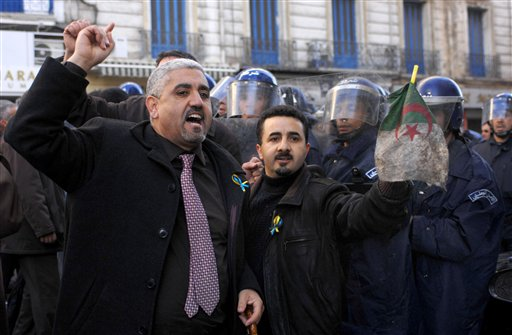 Demonstrators asking for political change in  their country face riot policemen in Algiers Saturday Jan. 22, 2011. Riot police have broken up a march by hundreds of protesters demanding Algeria overturn a law banning public gatherings. Some demonstrators waved Tunisian flags _ a nod to the street unrest that led Tunisia's president to flee to Saudi Arabia on Jan. 14. (AP Photo)