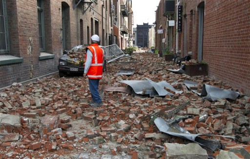 A worker looks at debris in central Christchurch February 24, 2011. International rescuers intensified their search for earthquake survivors in New Zealand on Thursday, despite fading hopes of finding any more people alive and fears that a damaged 26-storey tower could collapse nearby at any time.   REUTERS/Simon Baker