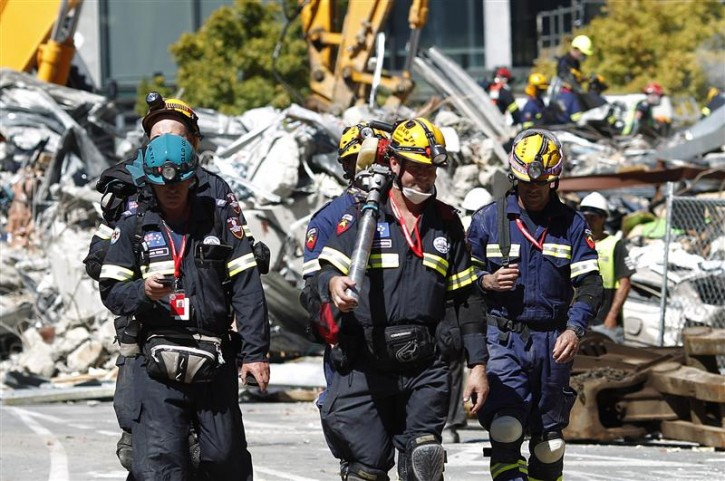 Rescue workers from Queensland in Australia walk past the rubble of the CTV building in Christchurch February 24, 2011 International rescuers intensified their search for earthquake survivors in New Zealand on Thursday, despite fading hopes of finding any more people alive. REUTERS/Tim Wimborne