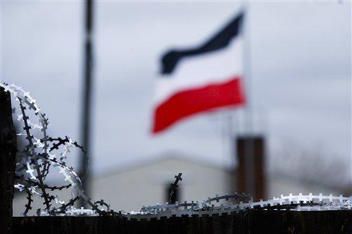 The national flag of the German Reich from 1871 to 1918 waves in the wind behind a barbed wire that secures the office of the far right German party NPD at Grevesmuehlen about 270 kilometer (168 Miles) north west of Berlin in the state Mecklenburg-Western Pomeraniaon, Germany, Tuesday, Jan. 25, 2011.  Grevesmuehlen is the neighboring town to the tiny ten house village of Jamel, where more than half of the residents are connected to the far right NPD Party and the Neo-Nazi scene. (AP Photo/Markus Schreiber)