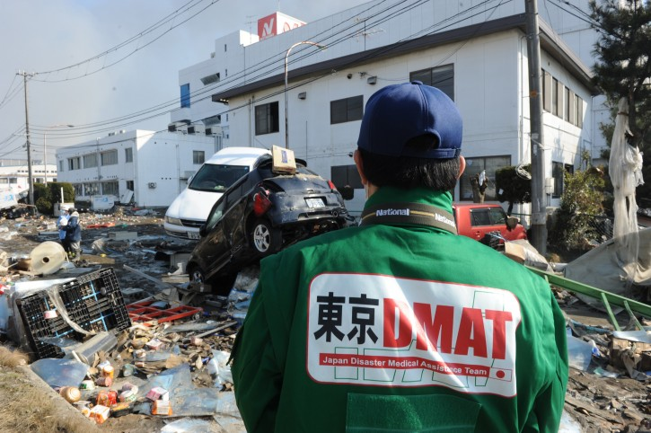 A 'Japan Disaster Medical Assistance Team' member looks at the scene of devastion at Sendai Port 13 March 2011 after an earthquake and tsunami  ravaged much of Japan's Pacific East coast on 11 March 2011. Japanese police say that the number of people killed in the disaster could surpass 10,000  EPA/ALEX HOFFORD