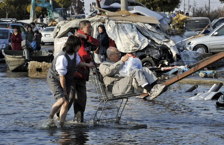 Two residents push an elderly man in a supermarket trolley through water brought by tsunamis in the devastated main street  in Ishinomaki, Miyagi Prefecture, northern Japan, about 270km north of Tokyo,13 March, 2011 after strong earthquakes and tsunami killing more than 1,000 people were hitting northern Japan and Japanese capital of Tokyo area on 11 March.  EPA/KIMIMASA MAYAMA