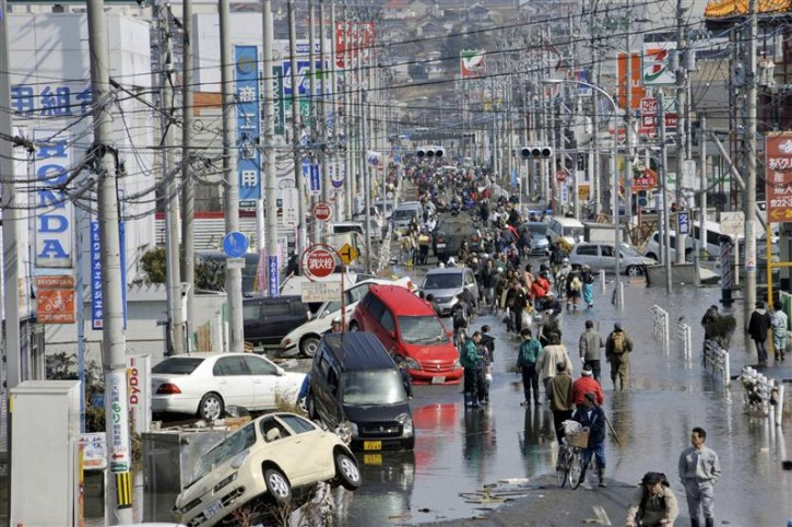People walk along a flooded street in Ishimaki City, Miyagi Prefecture in northern Japan, after an earthquake and tsunami struck the area, March 13, 2011. REUTERS/Kyodo