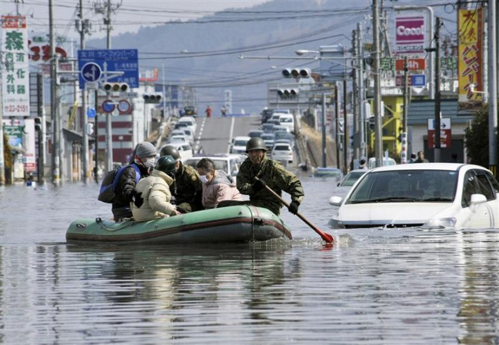 Japan Self Defence Forces troops rescue people from flooded areas in Ishimaki City, Miyagi Prefecture in northern Japan, after an earthquake and tsunami struck the area, March 13, 2011. REUTERS/Kyodo