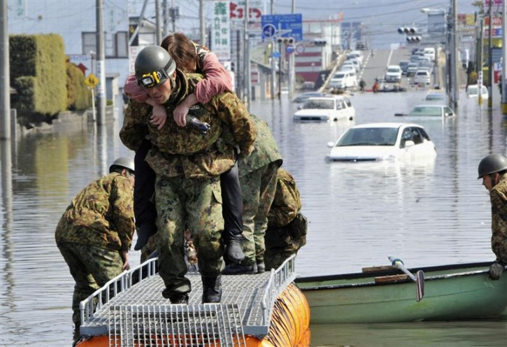 A woman is rescued from a flooded area by Japan Self Defense Forces troops in Ishimaki City, Miyagi Prefecture in northern Japan, after an earthquake and tsunami struck the area, March 13, 2011. REUTERS/Kyodo