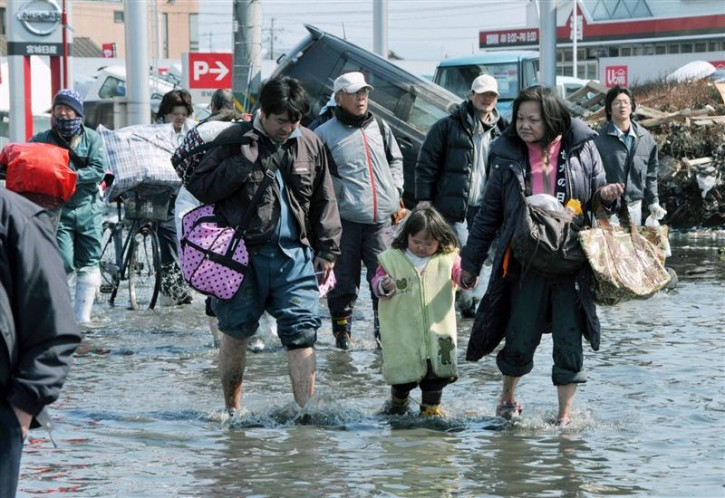 People walk through floodwaters caused by a tsunami in Ishimaki City, Miyagi Prefecture in northern Japan, after an earthquake and tsunami struck the area, March 13, 2011. REUTERS/Kyodo
