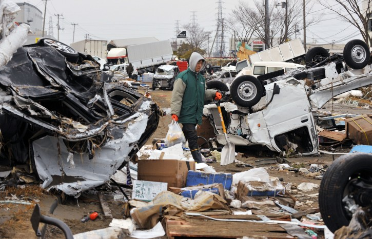 A resident walks between overturned vehicles as he heads for his parents' home in tsunami-devastated city of Tagajo, Miyagi Prefecture, northern Japan, about 220km north of Tokyo,13 March, 2011. Strong earthquakes and tsunamis  hit  northern Japan and Japanese capital of Tokyo area on 11 March. Japanese police say that the number of people killed in the disaster could surpass 10,000  EPA/KIMIMASA MAYAMA