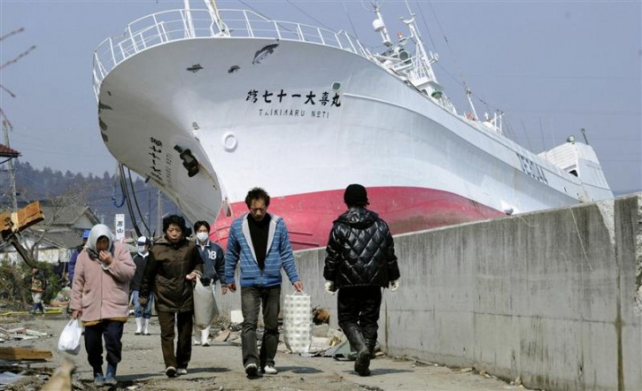 People walk in front of a tuna fishing boat tossed on to land in Kesennuma City, Miyagi Prefecture in northern Japan, after an earthquake and tsunami struck the area, March 13, 2011. REUTERS/Kyodo