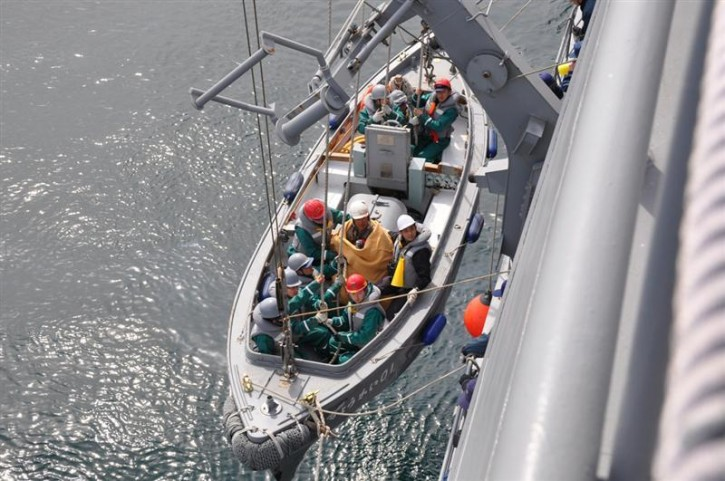 Sixty-year-old survivor Hiromitsu Shinkawa (C) who was swept out to sea by a tsunami is rescued by crew members of Japan Maritime Self-Defence Force (JMSDF) Aegis vessell Choukai about 15km (9 miles) off Fukushima prefecture, March 13, 2011. The crew of the JMSDF vessel found Hiromatsu clinging to the roof of his house on Sunday, two days after a tsunami caused by a massive earthquake swept him out to sea. The survivor is from Minamisoma, one of the cities worse hit by a powerful tsunami that has devastated parts of Japan's northeastern coast. REUTERS/