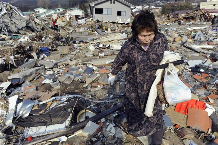 A woman searches for supplies amid piles of debris in Ofunato City, Iwate Prefecture in northern Japan, March 13, 2011. Japan faces a growing humanitarian crisis on a scale not seen since World War Two after its devastating earthquake and tsunami left millions of people without water, electricity, homes or heat. As officials on Sunday predicted the death toll could top 10,000, the country mobilised 100,000 soldiers to deliver food, water and fuel, and pull stranded survivors from buildings and damaged homes. More than 450,000 people had been evacuated. REUTERS/Kyodo