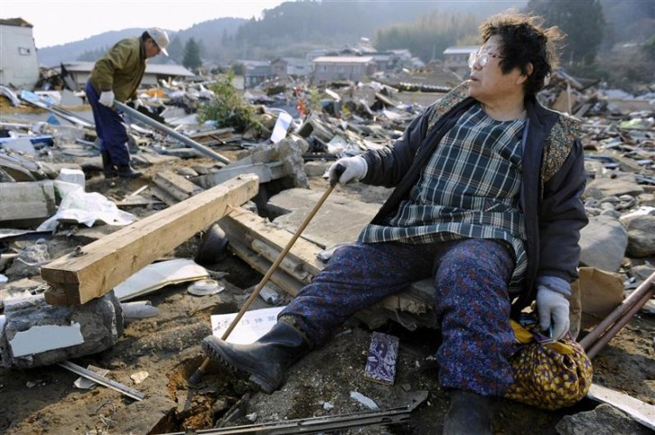 A woman looks out over the destroyed landscape in Ofunato City, Iwate Prefecture in northern Japan, after an earthquake and tsunami struck the area, March 13, 2011. Japan faces a growing humanitarian crisis on a scale not seen since World War Two after its devastating earthquake and tsunami left millions of people without water, electricity, homes or heat.  REUTERS/Kyodo